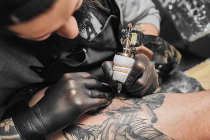 Tattoo master is tattooing in the tattoosalon